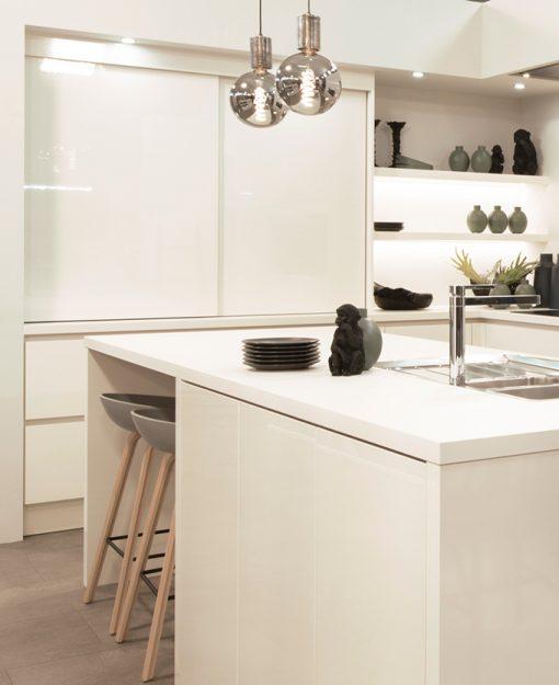 Kleuraccenten vallen goed op in deze witte, minimalistische keuken